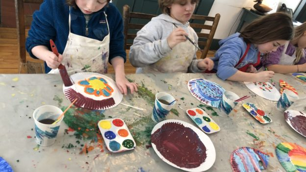 Campers painting on paper plates.