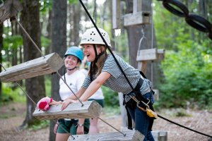 A smiling Hiver about to go up the rope ladder at the ropes course.
