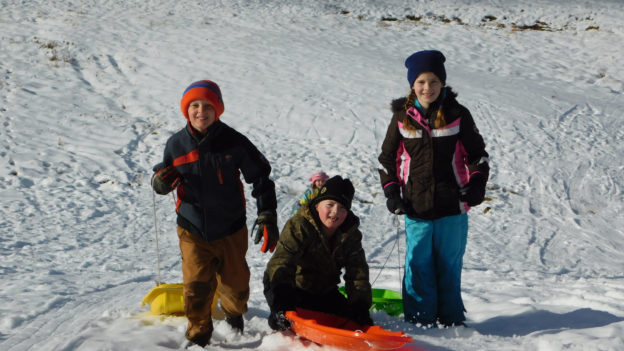 A group of kids with sleds smiling on a snowy hill.