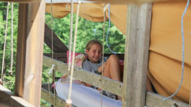 A camper relaxing in an open air cabin.