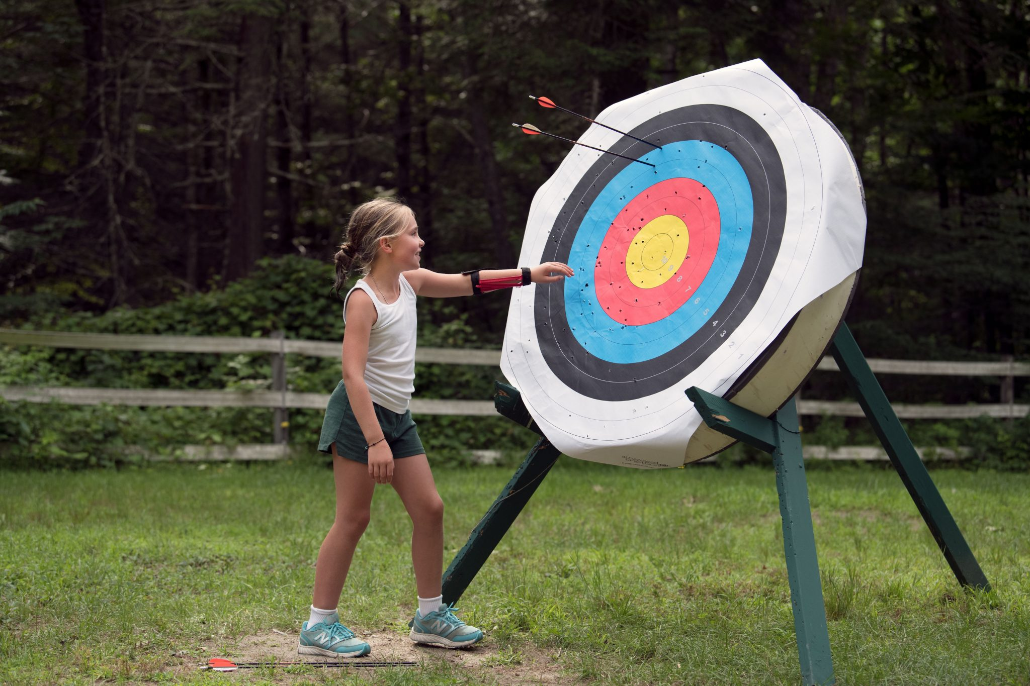 A young Hiver approaching a target with arrows in it.