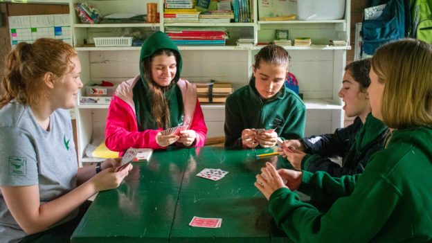 A group of campers playing card games.