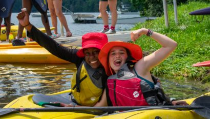 Two campers on their own kayaks, posing together.
