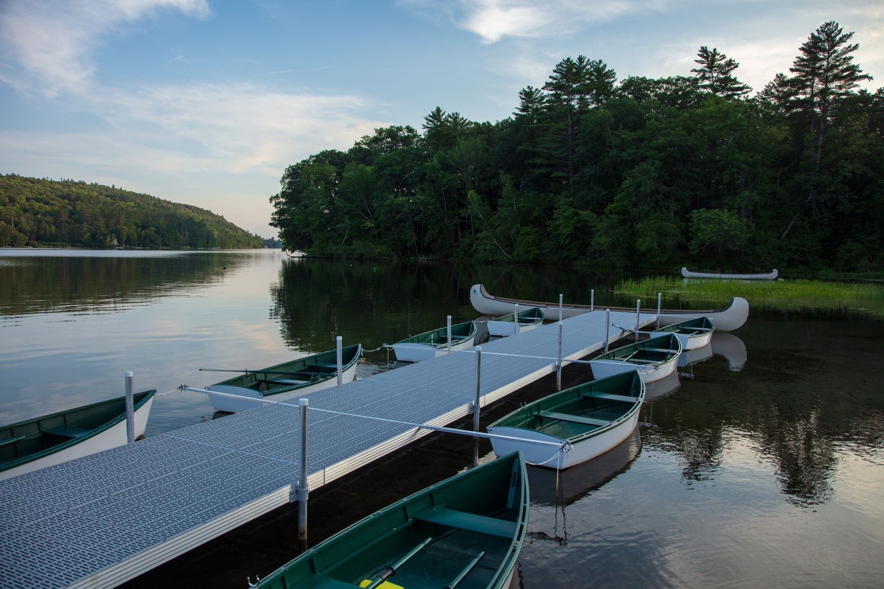 A bunch of row boats next to the docks on the lake.