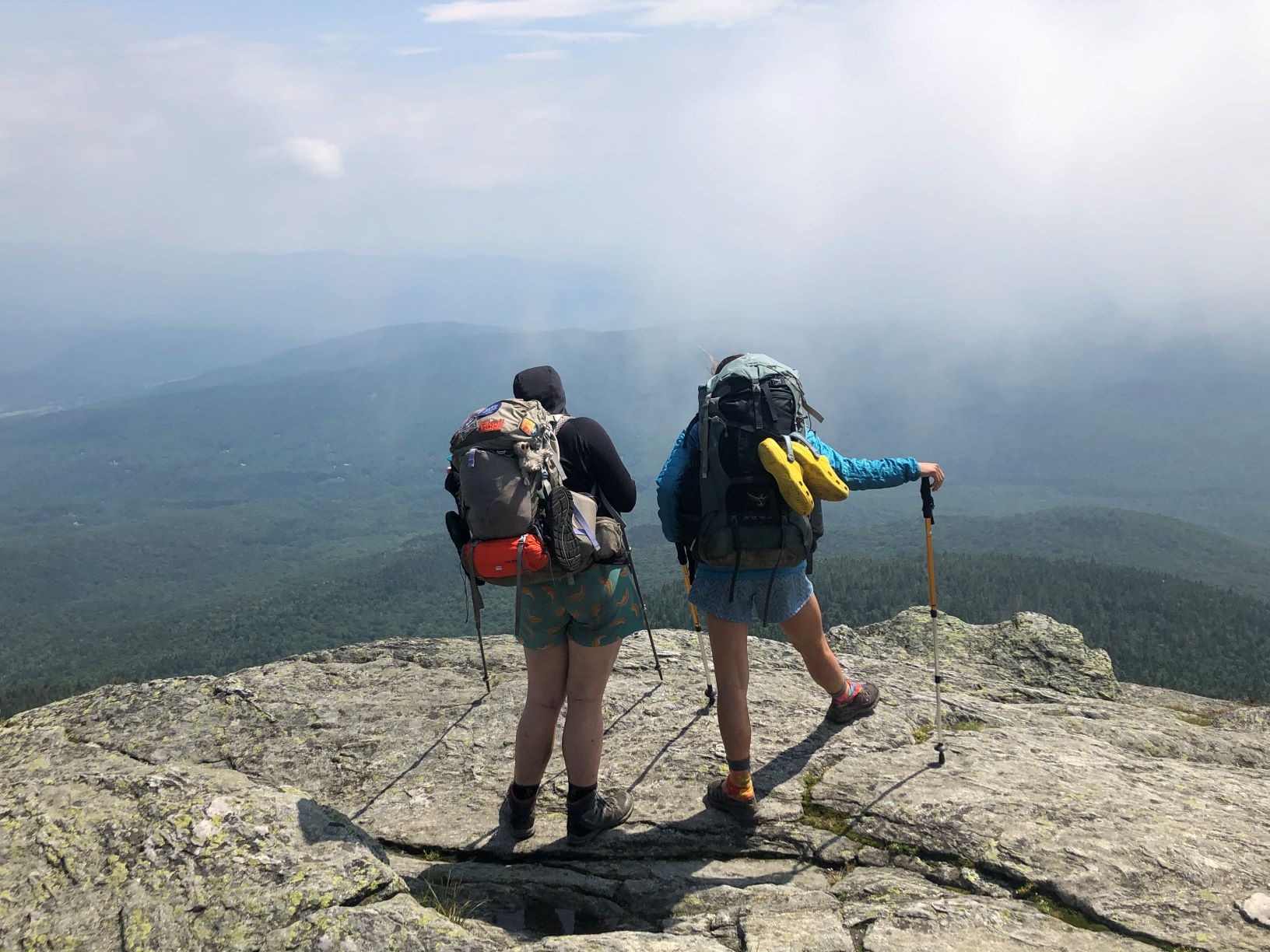 Two hikers on top of a mountain facing out.