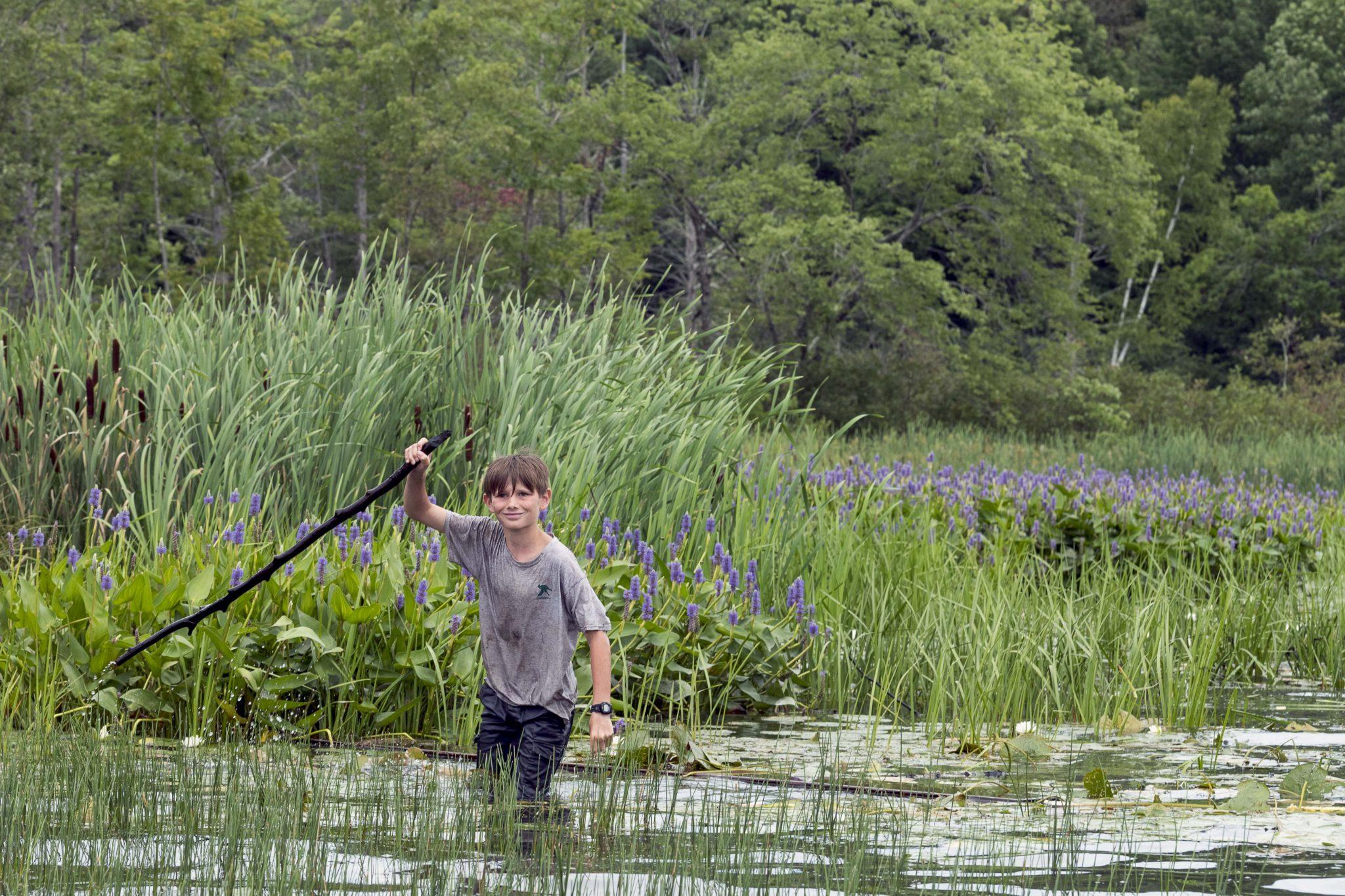A Lanakila camper walking through the swamp holding a walking stick.