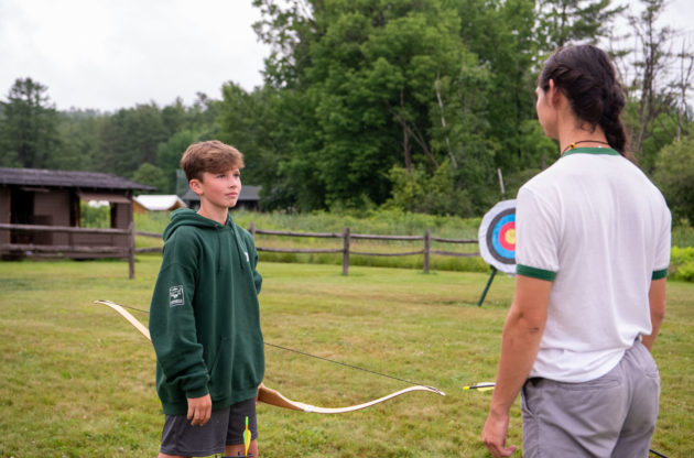 Campers learning how to shoot a bow and arrow.