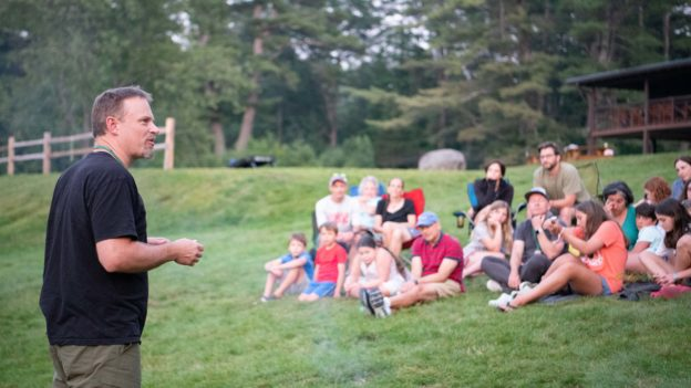 A man speaking to campers outside.