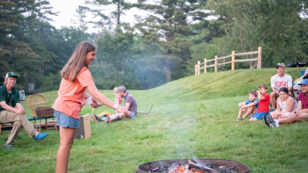 A camper throwing a stick into a firepit.
