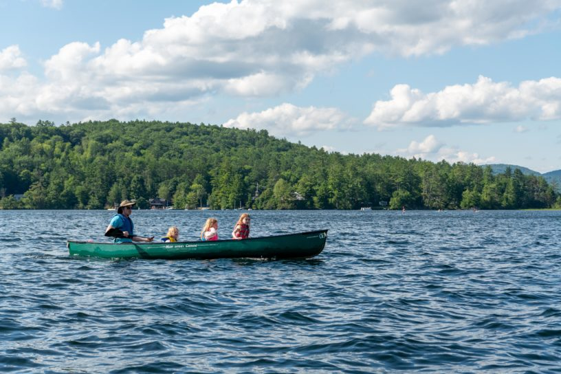 A counselor and three campers paddling in a green canoe across the lake.