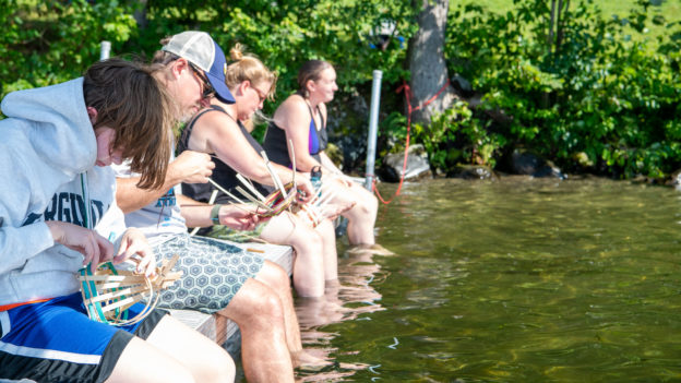 Campers weaving baskets while dipping their feet in a lake.