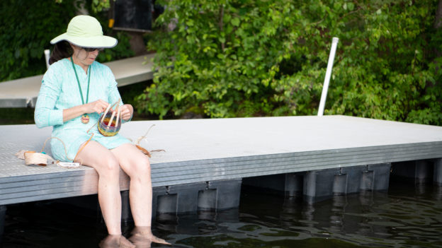 A woman weaving a basket while sitting on a dock.