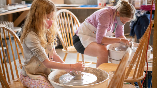 A young camper doing pottery.