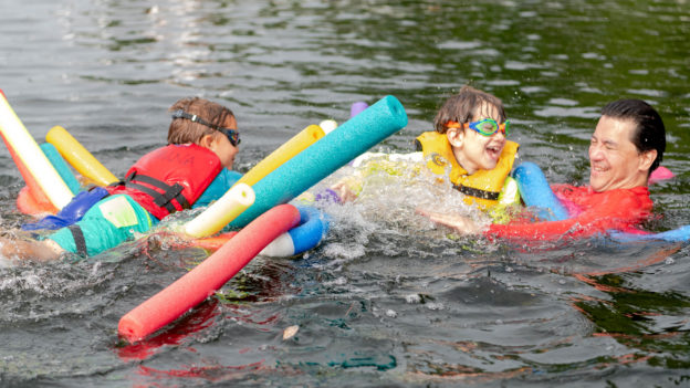 Campers swimming in a lake with colorful pool noodles.