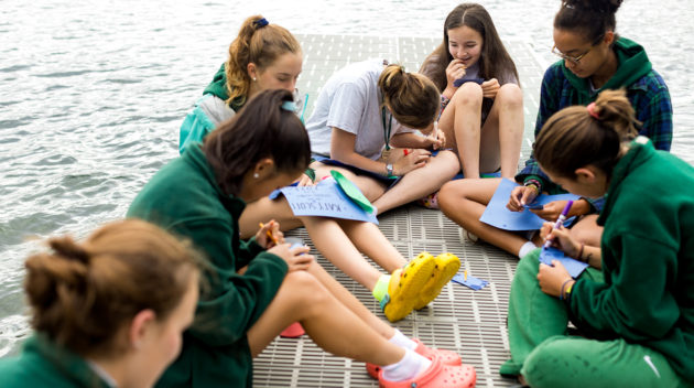 A group of Aloha campers sitting and drawing on the docks.