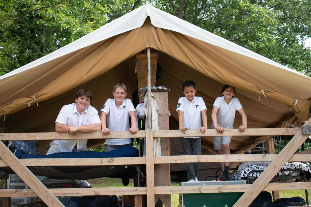 Four campers in an open air cabin.