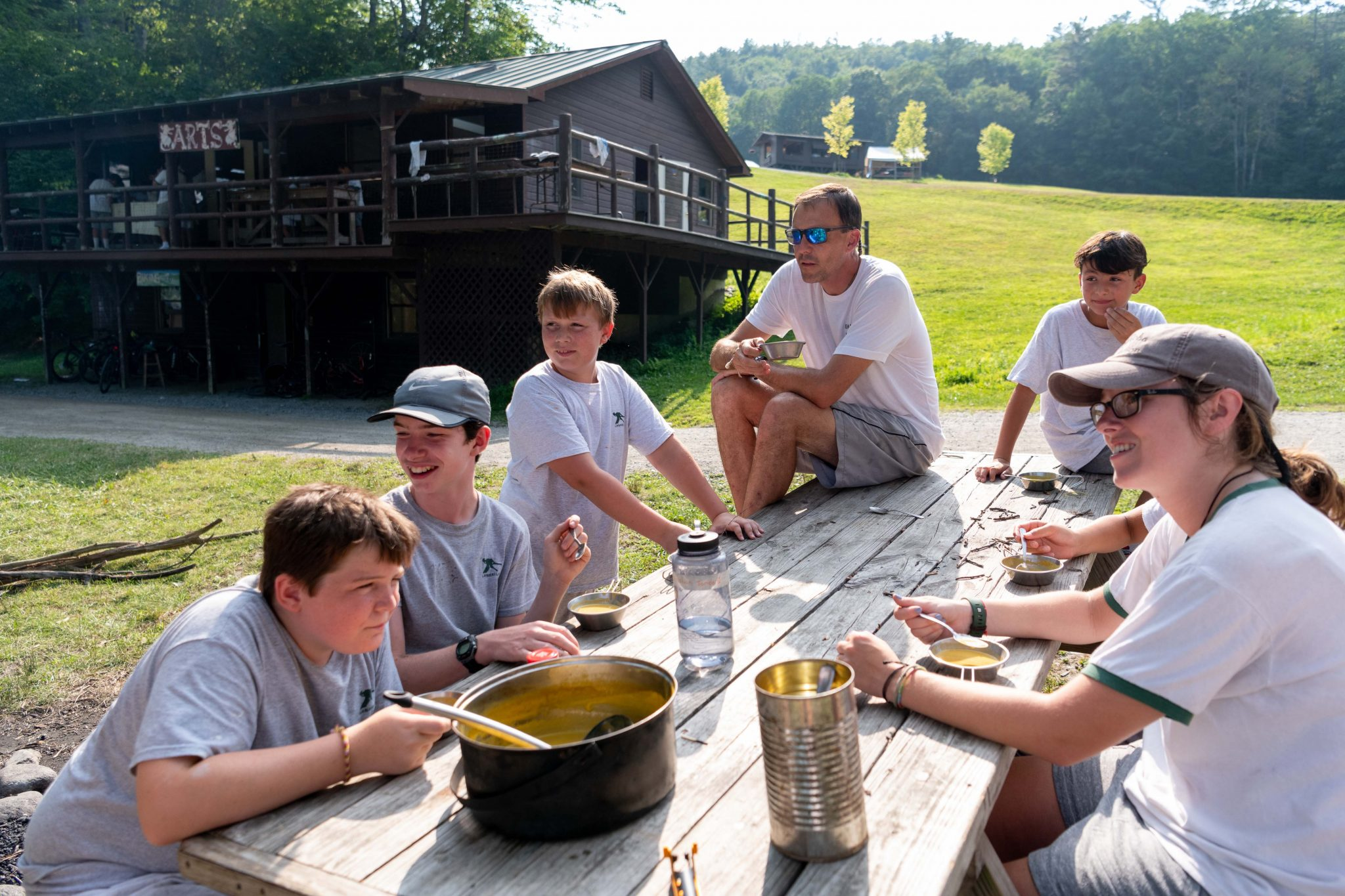 A group of Lanakila campers and counselors with Ridge eating soup they made over a fire.
