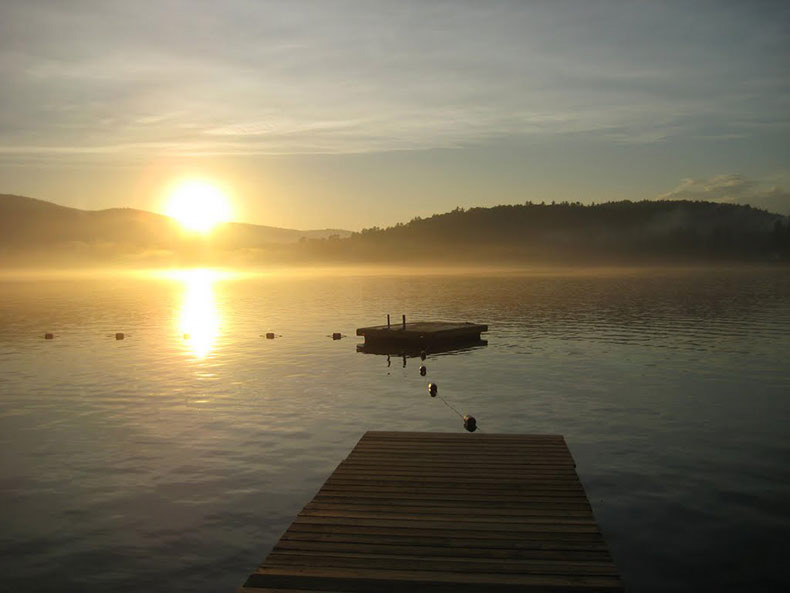 The sun rising over the mountains overlooking the lake.