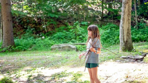 A young camper holding a bunch of twigs.