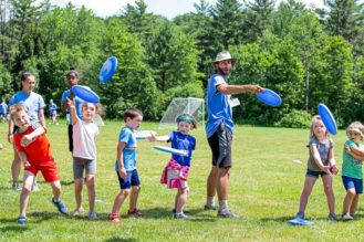 Young campers and a counselor throwing blue frisbees.