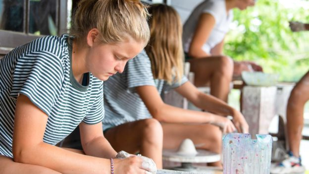 A camper working on pottery.