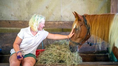 A girl petting a horse.