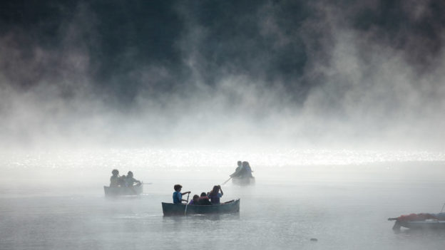 A lake shrouded in mist with people on canoes.