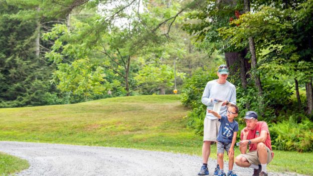 A child and two adults on a trail.