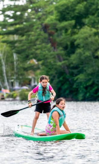 Two young girls paddle boarding.