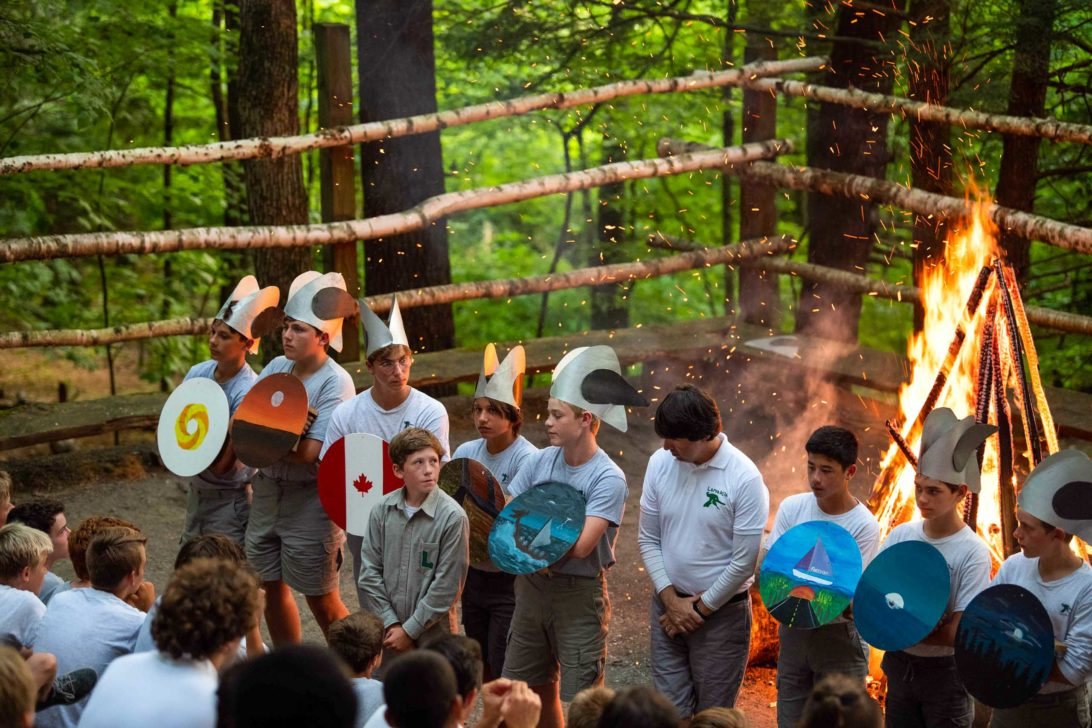 A group of campers performing in front of a campfire.
