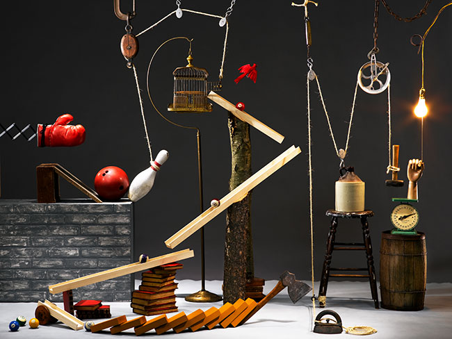 A rube goldberg machine featuring dominos, a bowling pin, and a tiny axe.
