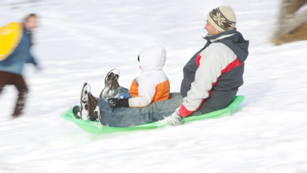 A father and child sledding down a hill together.