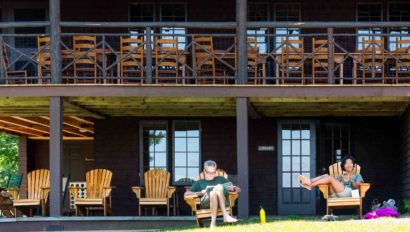 Two people relaxing on lawn chairs in front of a lodge.
